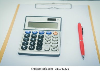button of calculator with pen on the white blank paper