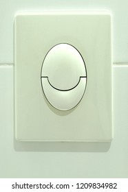 The button of a flush tank of a toilet bowl with two levels for an economical consumption of water.