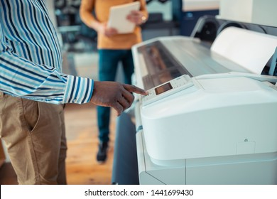 Button on printer. Close up of dark-skinned worker pressing button on printer while printing posters