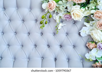 Buttoned luxury pattern with flowers, copy space. Capitone textile background. Chesterfield style, checkered soft fabric furniture upholstery, diamond pattern, decoration with buttons, close up