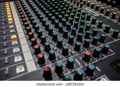 Buttons and knobs with slider in various parts of Sound mixer control panel or Audio mixer board console in the audio control room