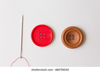 Buttons and a needle on a white background. Business and hobbies. Needlework.