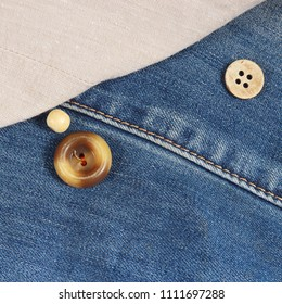 Buttons on the background of canvas and jeans clothes close up