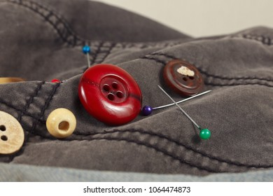 Buttons, pins and needles on cotton clothes close up