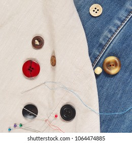 Buttons, pins and needles with threads on the background of cotton and jeans clothes close up