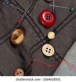 Buttons, pins and needles with threads on black cotton and blue jeans clothes close up