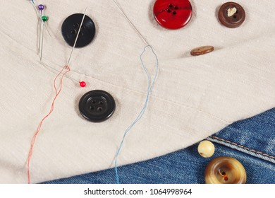 Buttons, pins and needles with threads on cotton and denim close up