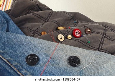 Buttons, pins and needles with threads on the background of black cotton and blue jeans clothes close up