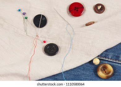 Buttons, pins and needles with threads on canvas and denim close up
