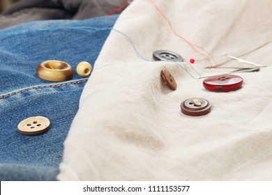 Buttons, pins and needles with threads on cotton and jeans clothes close up