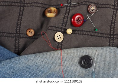 Buttons, pins and needles with threads on black cotton and blue denim close up