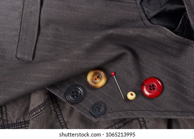 Buttons and pins on the background of black cotton clothes close up