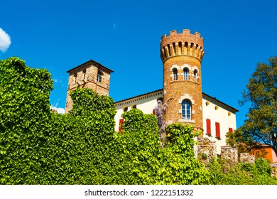Buttrio castle brick tower seen from outide the perimeter crenellated wall covered in ivy, Udine, Friuli, Italy