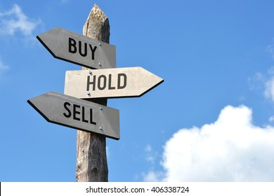 """""""Buy, hold, sell"""" - wooden signpost, cloudy sky"""