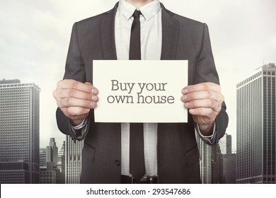 Buy a house on paper what businessman is holding on cityscape background