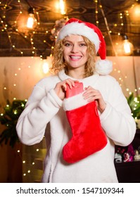Buy or knit your Christmas stocking and stuff them with special goodies. Woman hold red stocking. New year celebration. Stockings filled with many fun things, called Christmas stocking stuffers.