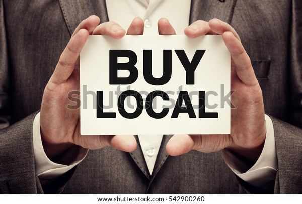 Buy Local. Businessman holding a card with a message text written on it