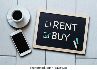 Buy not rent blackboard concept. Choosing buying over renting with coffee and mobile phone on background
