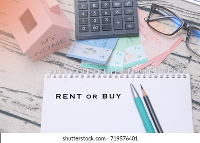 Buy not rent notepad concept. Choosing buying over renting with model house, calculator, Malaysian ringgit, spectacles and notepad
