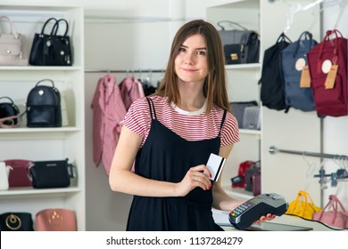 Buy. Pay for the purchase through a credit card using the terminal. Small business. Woman is a salesman in a clothing store.