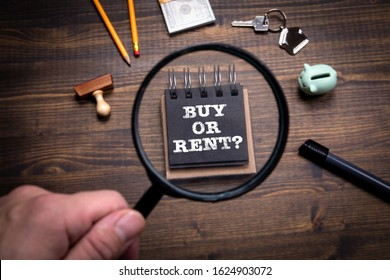Buy or Rent. Real Estate, Banking, Finance and Tax Concept. Man's hand, holding magnifying glass