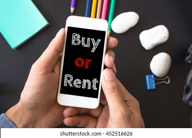 Buy or rent, text message on screen at hands take smartphone, black table with office supplies backdrop background . business concept.