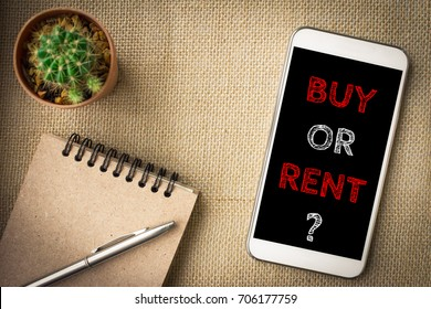 Buy or rent, text message on screen smartphone, brown table with office supplies backdrop background . business concept.
