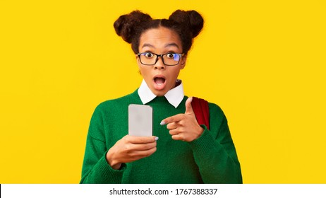 Buy This. Amazed black schoolgirl pointing at smartphone, looking at camera on yellow background. Panorama, free space