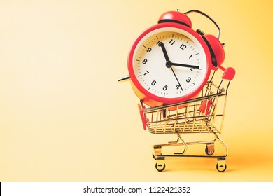 Buy time, Shopping cart with red vintage alarm clock show 10 O'clock over yellow background