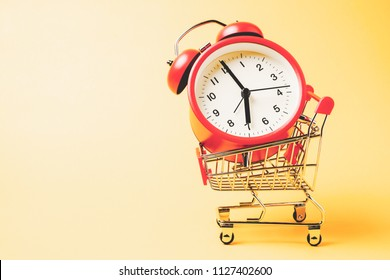 Buy time, Shopping cart with red vintage alarm clock show 7 O'clock over yellow background