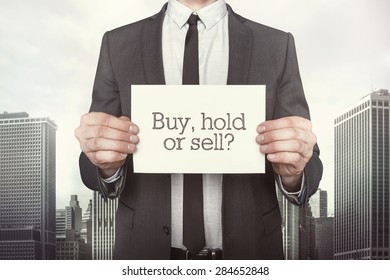 Buy vs hold or sell on paper what businessman is holding on cityscape background