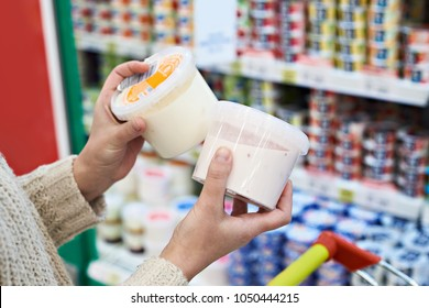 Buyer hands with plastic yogurt jars at the grocery store
