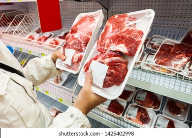 Buyer hands with pork meat packages at the grocery store. Man choosing meat in shop. People buying grocery. Meat in vacuum packing