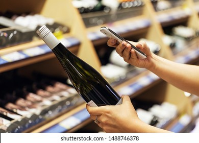 The buyer photographs a bottle of wine, a mystery shopper. Checking the quality of the goods by barcode