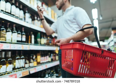 A buyer with a red wine basket chooses wine in the alcohol store of the store.