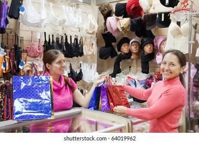 Buyer  and salesman  with purchases at  counter in underwear shop. Focus on buyer