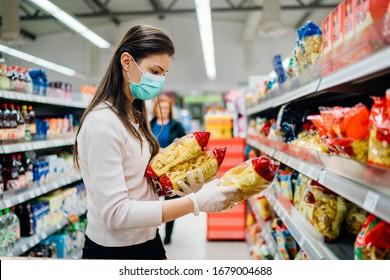 Käufer mit einer Schutzmaske.Einkauf während der Pandemie-Quarantäne.Nicht verderbliche intelligente Haushaltsartikel gekauft Vorbereitung.Frau kaufen wenige Nudelpakete.Budget Nudeln und Nudeln.