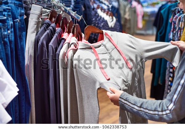 Buyer woman chooses clothes in the store