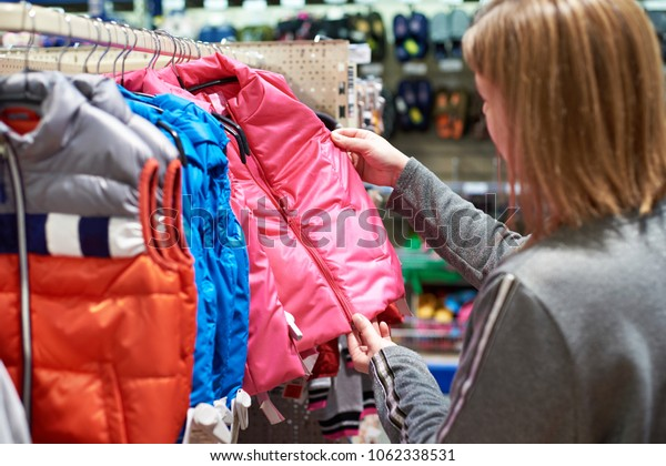Buyer woman chooses kid jacket clothes in the store
