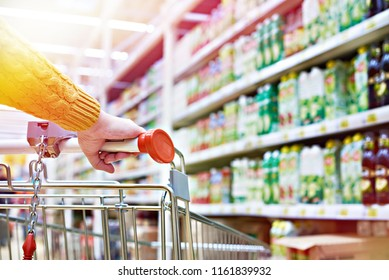 Buyers hand on shopping cart in store shelves
