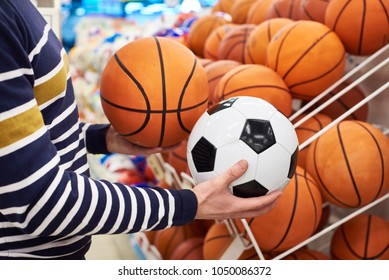 Buyer's hands with football and basketball in the sports shop