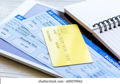 Buying airline tickets online with credit cards on table background