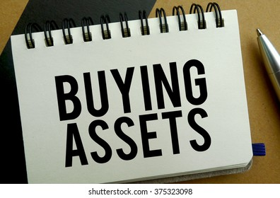 Buying assets memo written on a notebook with pen