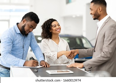 Buying Car. Black Couple Shaking Hands With Salesman And Signing Papers In Cars Selling Center. Selective Focus