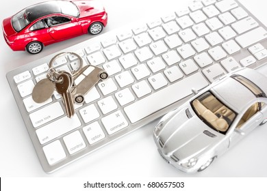 Buying car online. Car keys and toy car on keyboard on white background top view