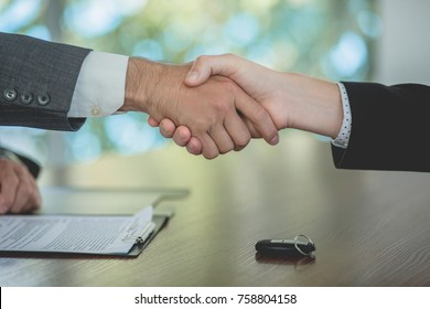 Buying a car, sales manager and buyer shakig hands. Close up view of handshake between two men.