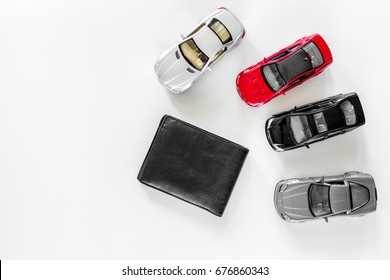 Buying car. Toy cars and wallet on white background top view copyspace