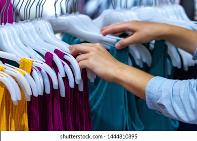 Buying cloth on second hand market in shopping center. Sales and discount. Woman shopping in fashion mall, choosing new clothes for wardrobe update