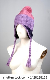 Buying colorful female hat with ears of rope on long winter wool woman accessory hat fashion trend lifeless mannequin head on grey background.