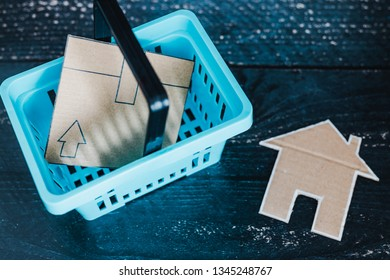 buying decor items or furniture concept: shopping basket with parcel and small cardboard house next to it